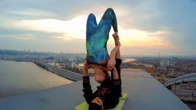 Couple doing acrobatic tricks on top of bridge, adrenaline junkies, risky hobby. Stock photo royalty free stock photo