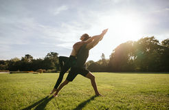 Couple doing acrobatic yoga exercise at park Royalty Free Stock Image