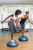 Couple doing aerobics on bosu balls Royalty Free Stock Image