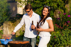 Couple doing BBQ in garden in summer Stock Photos
