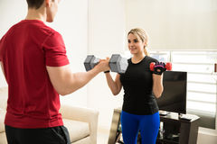 Couple doing bicep curls together Royalty Free Stock Photos