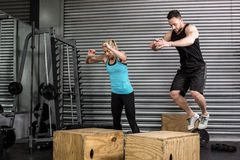 Couple doing box jumps in gym stock photography
