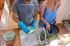 Couple doing the dishes. Over view of couple doing household chores in the kitchen Stock Photography
