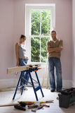 Couple doing DIY at home, woman holding glue gun beside timber on workbench, smiling, portrait Stock Photo