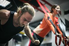 Couple doing exercises in a gym with straps. Young sporty people Stock Photo