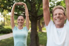 Couple doing exercises in the park. They do stretching hands royalty free stock photos