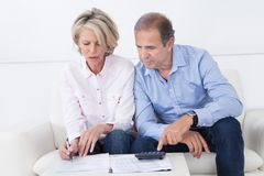 Couple doing family finances at home. Mature couple doing family finances at home Royalty Free Stock Images