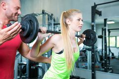 Couple doing a fitness workout in the sport gym. Young sexy couple is doing a fitness workout in the sport gym. personal trainer. dumbbells, barbells and some Royalty Free Stock Photography