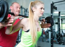Couple doing a fitness workout in the sport gym. Young sexy couple is doing a fitness workout in the sport gym. personal trainer. dumbbells, barbells and some Royalty Free Stock Images