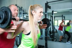 Couple doing a fitness workout in the sport gym. Young sexy couple is doing a fitness workout in the sport gym. personal trainer. dumbbells, barbells and some Stock Images