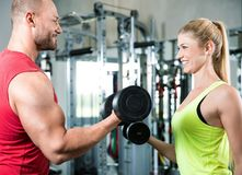 Couple doing a fitness workout in the sport gym. Young sexy couple is doing a fitness workout in the sport gym. personal trainer. dumbbells, barbells and some Stock Photo