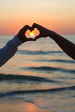 Couple doing heart shape with their hands on beachside Stock Photo