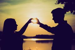Couple doing heart shape with their hands on lake shore. Royalty Free Stock Photography