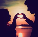 Couple doing heart shape with their hands on lake shore. Royalty Free Stock Image