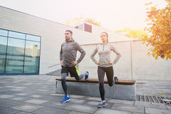 Couple doing lunge exercise on city street Royalty Free Stock Photos