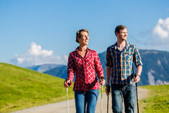 Couple doing nordic walking exercise in mountains. With alpine panorama Stock Photos