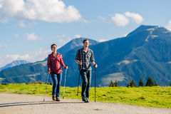 Couple doing nordic walking exercise in mountains. With alpine panorama Stock Images