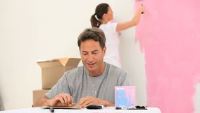 Couple doing painting work. In a room stock footage
