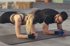 Couple doing a plank exercise. Couple working out on a building rooftop terrace, doing a plank exercise. Focus on the man stock photos