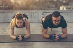 Couple doing a plank exercise. Couple working out on a building rooftop terrace, doing a plank exercise stock photo
