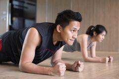 Couple doing plank. Young asian couple doing plank in gym royalty free stock image