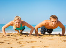 Couple doing push ups on the beac. Athletic couple doing push ups on the beach, workout training royalty free stock images