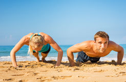 Couple doing push ups on the beac Royalty Free Stock Photo