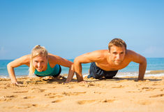 Couple doing push ups on the beach. Athletic couple doing push ups on the beach, workout training Royalty Free Stock Images
