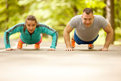 Couple doing push-ups at the park.Workout outdoors. Royalty Free Stock Images
