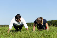 Couple doing push ups in summer grass Stock Images