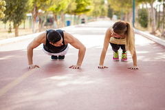 Couple doing push ups together. Young couple warming up and doing some push ups together outdoors Stock Photos