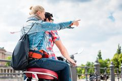 Couple doing a scooter trip in Berlin. Young couple, women and man, doing a scooter trip to the Berlin Museum Island Stock Photography