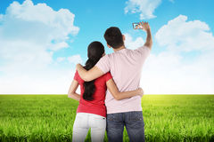 Couple doing selfie in the middle of the meadow Stock Images