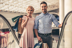Couple doing shopping. Beautiful couple with shopping bags is looking at camera and smiling while standing on the escalator in the shopping mall Royalty Free Stock Images