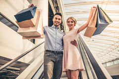 Couple doing shopping. Beautiful couple with shopping bags is looking at camera and smiling while standing on the escalator in the shopping mall Stock Photo