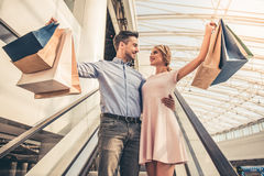 Couple doing shopping. Beautiful couple with shopping bags is looking at each other and smiling while standing on the escalator in the shopping mall Royalty Free Stock Images