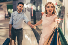 Couple doing shopping. Beautiful couple with shopping bags is doing shopping in the mall. Excited girl is pulling her tired boyfriend stock image