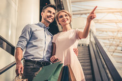 Couple doing shopping. Beautiful couple with shopping bags is talking and smiling while doing shopping in the mall royalty free stock image