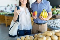 Couple Doing Shopping In Food Store With Credit Card royalty free stock images