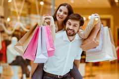 Couple doing shopping. Happy beautiful young couple holding shopping bags while standing in mall. Woman pickaback Royalty Free Stock Image