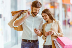 Couple doing shopping. Happy beautiful young couple smiling, holding shopping bags and using smart phones while standing in mall stock photo