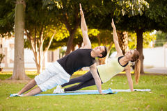 Couple doing a side plank yoga pose. Good looking young couple practicing some yoga in a park and doing a side plank together stock photos