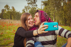 Couple doing silly and funny faces while taking selfie picture w. Ith their mobile phone in field of red poppies royalty free stock photos