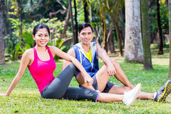 Couple doing sit-up in tropical Asian park Royalty Free Stock Photo