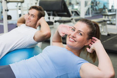 Couple doing sit ups on exercise balls Stock Image