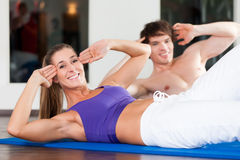 Couple doing sit ups in gym Stock Image