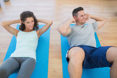 Couple doing sit ups at gym Royalty Free Stock Photo
