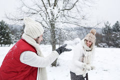 Couple doing snowball fight. Happy couple doing a snowball fight together in winter Royalty Free Stock Photography