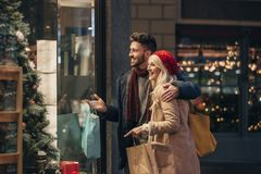 Couple Doing Some Window Shopping. Side view of a couple doing some window shopping at christmas. The mid adult male has his arm around the mid adult female and royalty free stock images