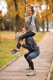 A couple are doing sports in an autumn park. The guy crouches holding the girl on his shoulders. Stock Images